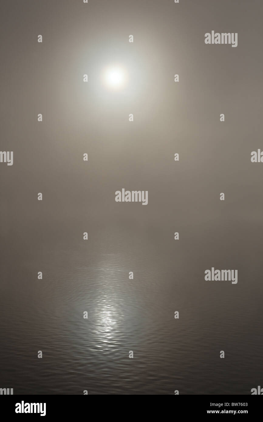 The sun reflecting on a misty lake - Stock Image