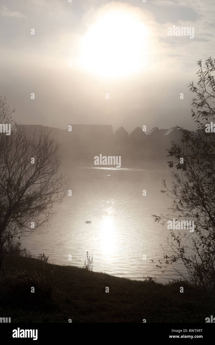 Outline of houses in the distance next to a misty lake Stock Photo
