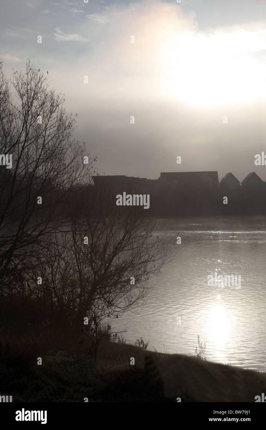 A foggy morning at a lake with houses in the distance, the sun shimmering on the water. - Stock Image