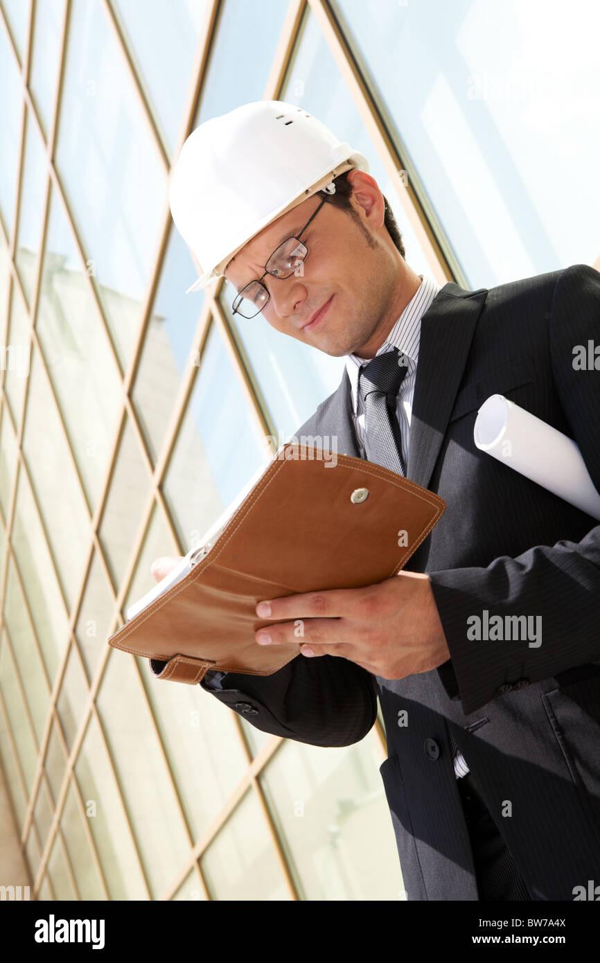 Portrait of confident foreman in helmet making business plan - Stock Image