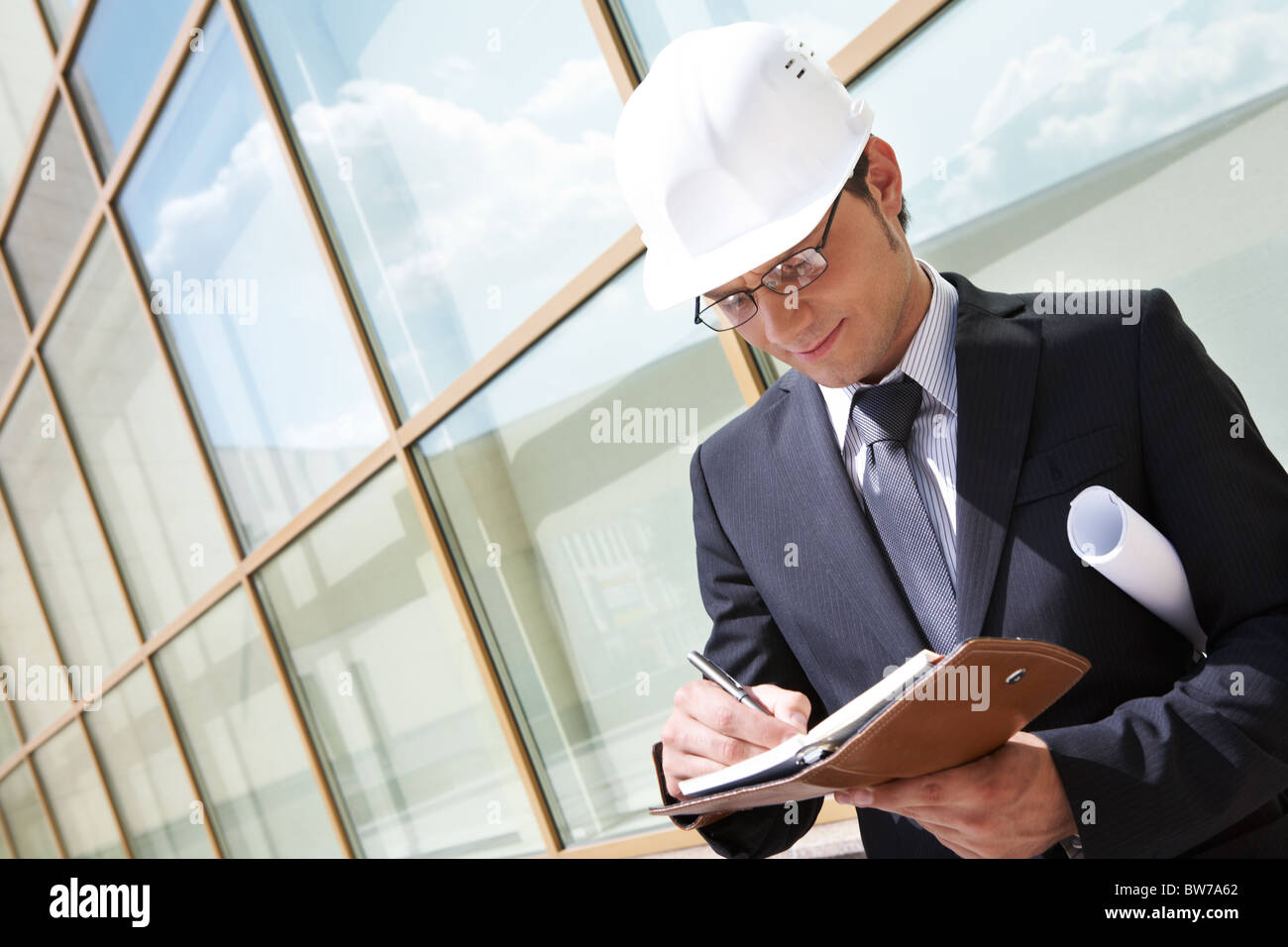 Portrait of confident foreman in helmet writing business plan - Stock Image