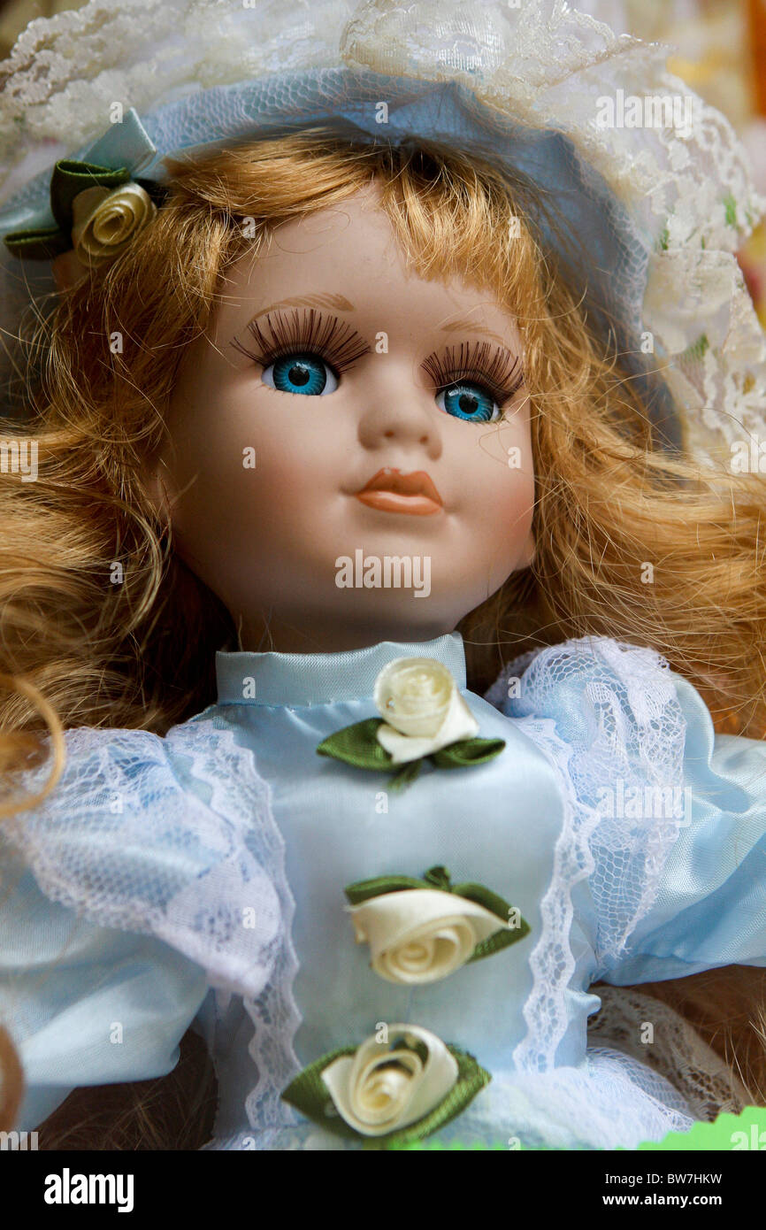 Porcelain doll with blonde hair and blue eyes - Stock Image