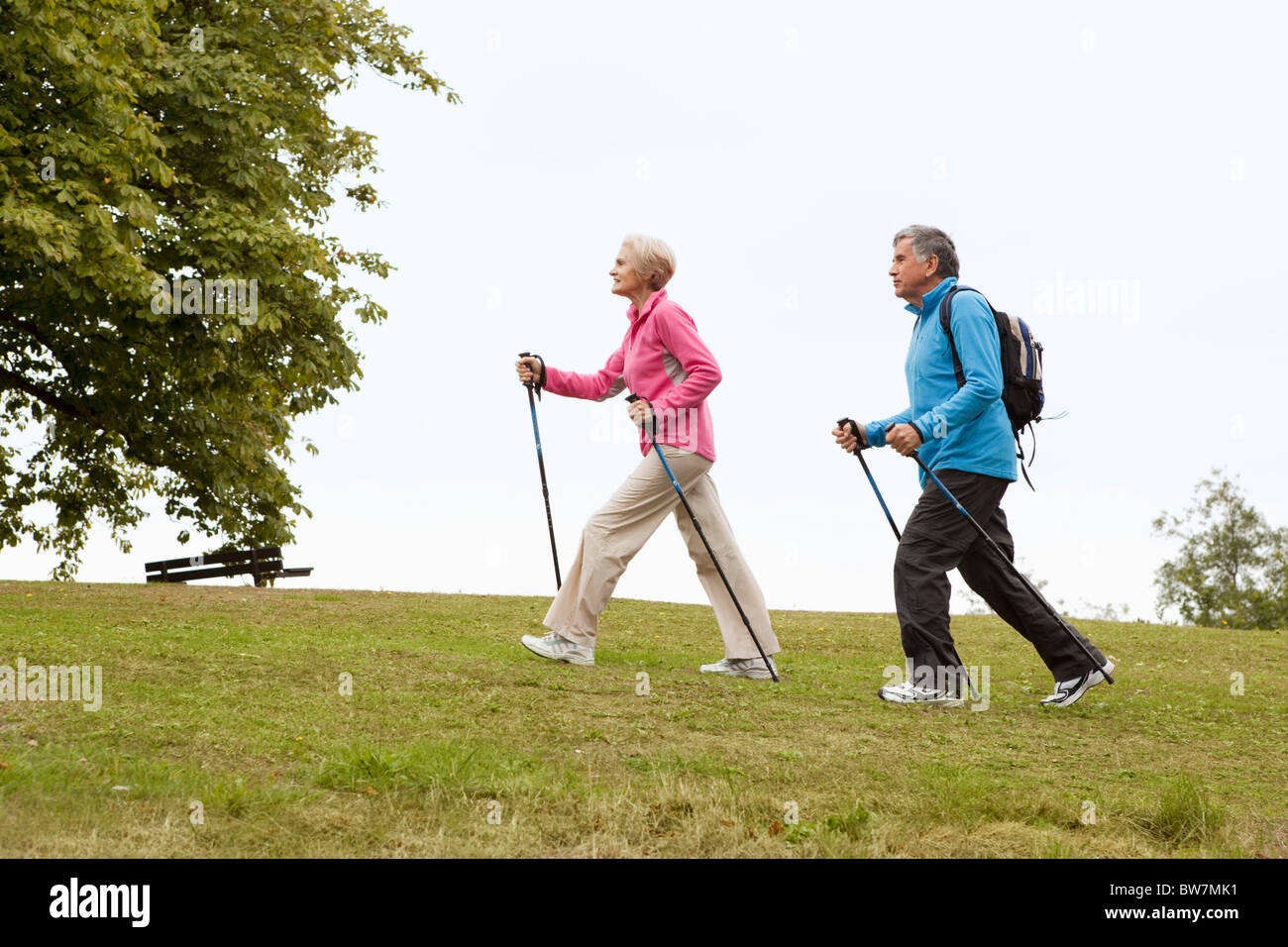 Mature couple nordic walking in park - Stock Image