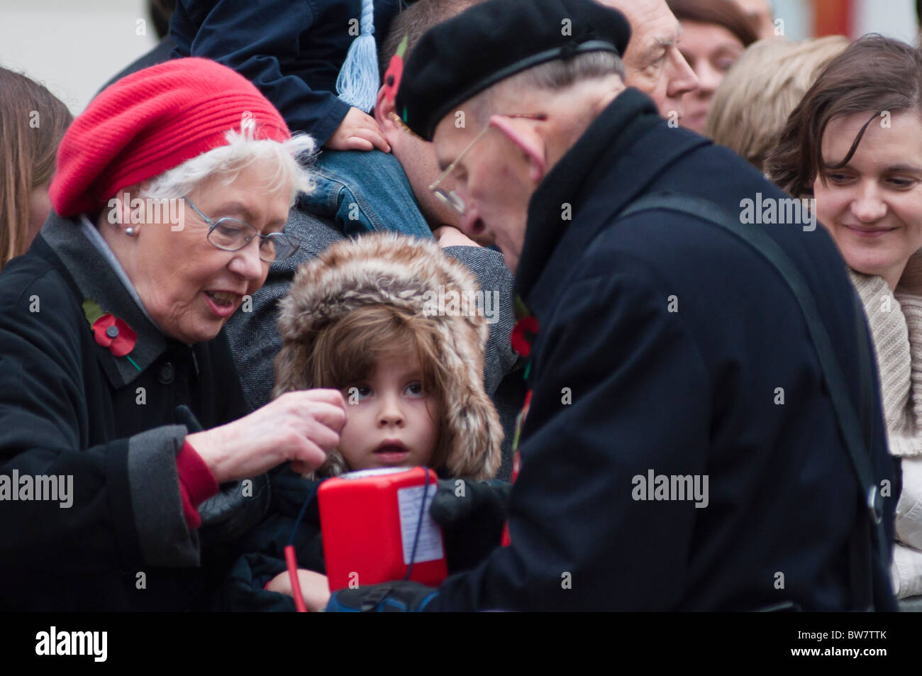 Old lady buys a poppy during the Lord Mayor's parade in London 2010. - Stock Image