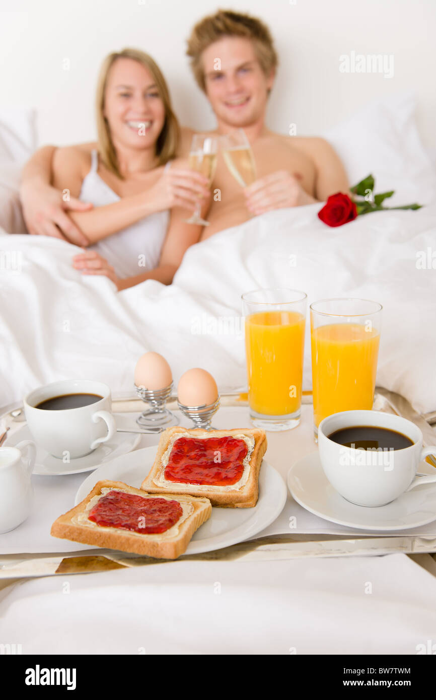 Luxury hotel honeymoon breakfast couple in white bed together