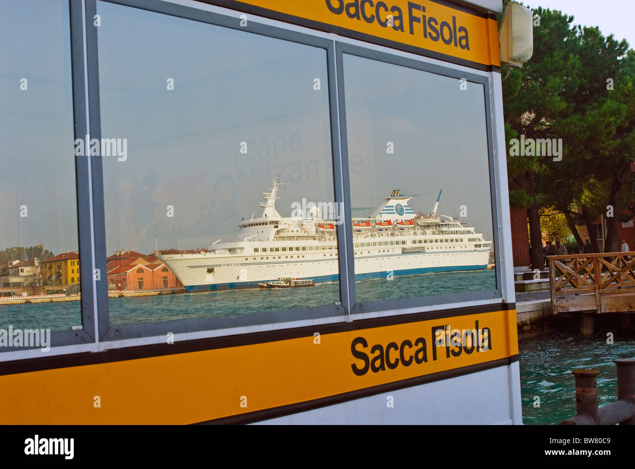 The cruise liner Delphin seen reflected in the windows of the vaporetto stop at Sacca Fisola, Venice - Stock Image