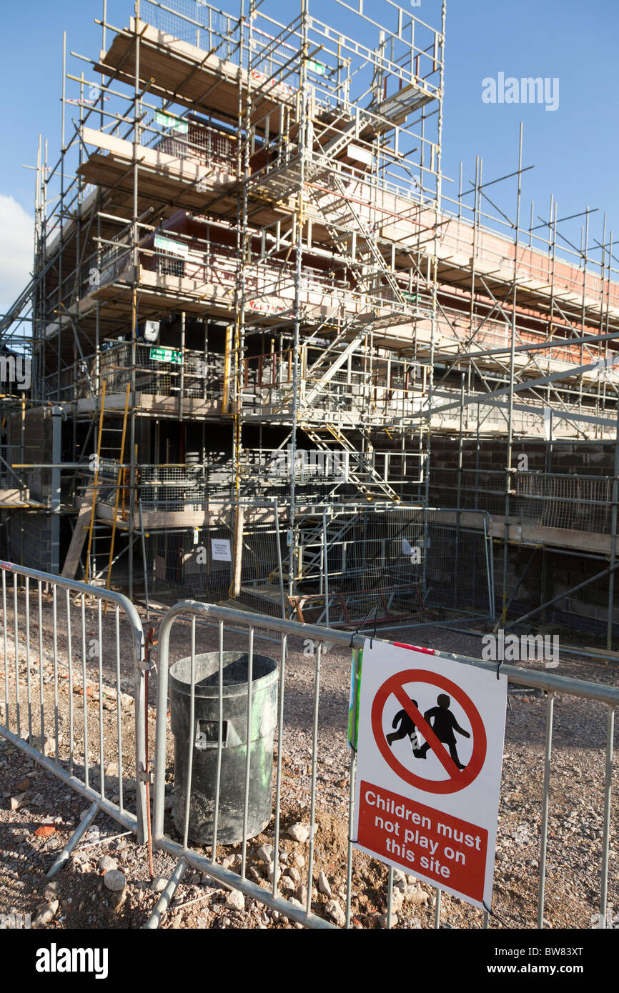 scaffolding covering new building under construction with warning sign children must not play on this site - Stock Image