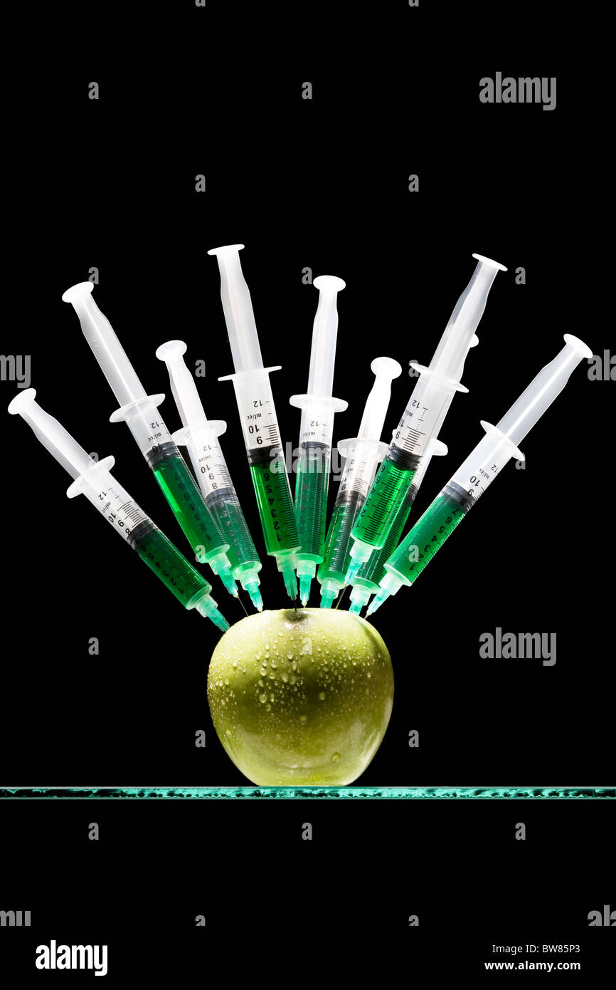 Syringes stuck in an apple - Stock Image