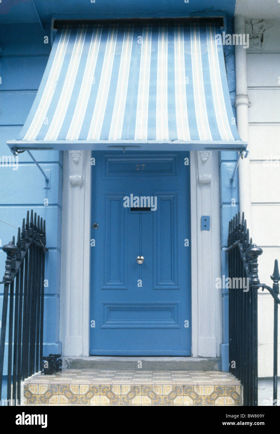 Close Up Of Blue+white Striped Awning Above Blue Front Door In Pale Blue  Traditional House