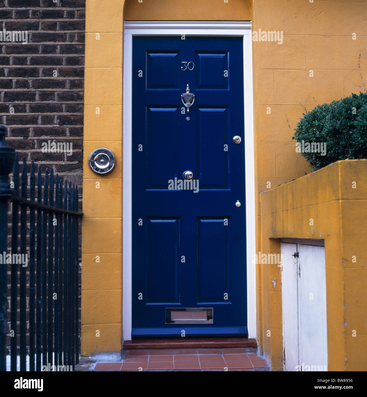 Close Up Of Blue Front Door On Traditional Dark Yellow Painted House