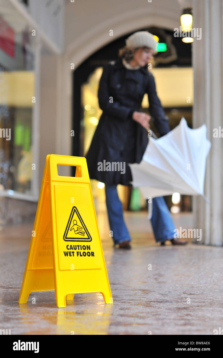 woman with umbrella on wet floor - Stock Image