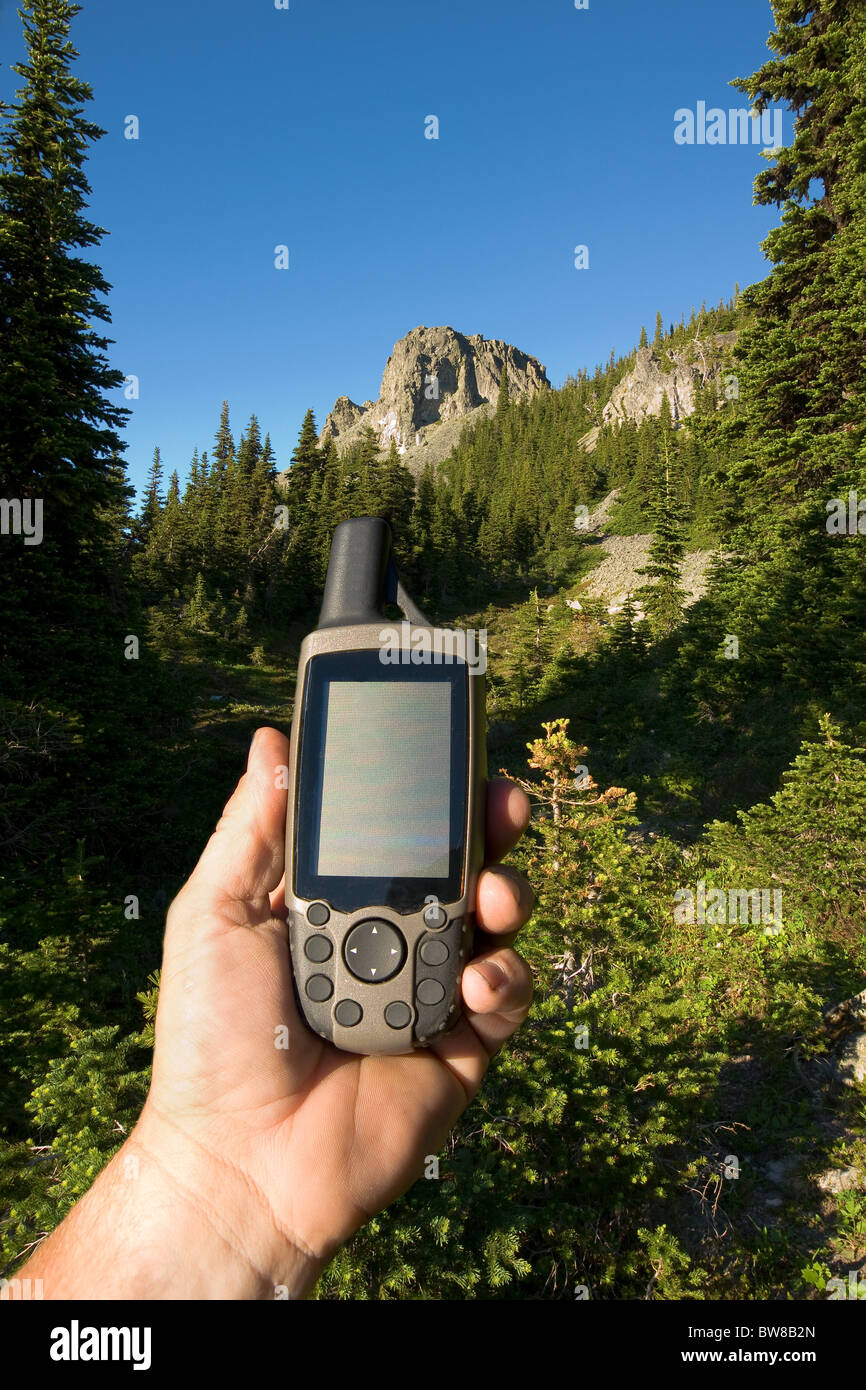 A hand holding a GPS for determining exact location - Stock Image