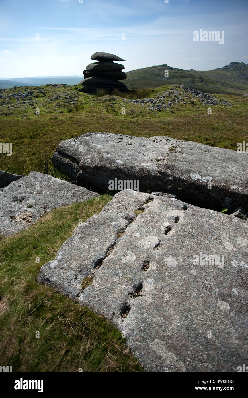 Granite boulder marked with stone working holes, the Showery Tor cheesewring in the middle distance, and Rough Tor Stock Photo