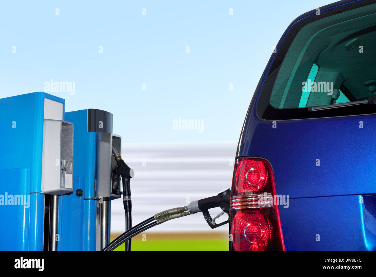 At the gas station pump putting gas into the car - Stock Image
