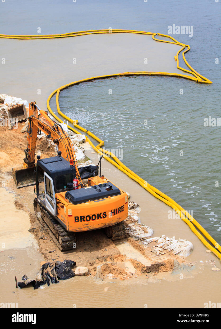 A digger used to repair the Mounts Bay Road river wall beside the Swan River in Perth, Western Australia - Stock Image