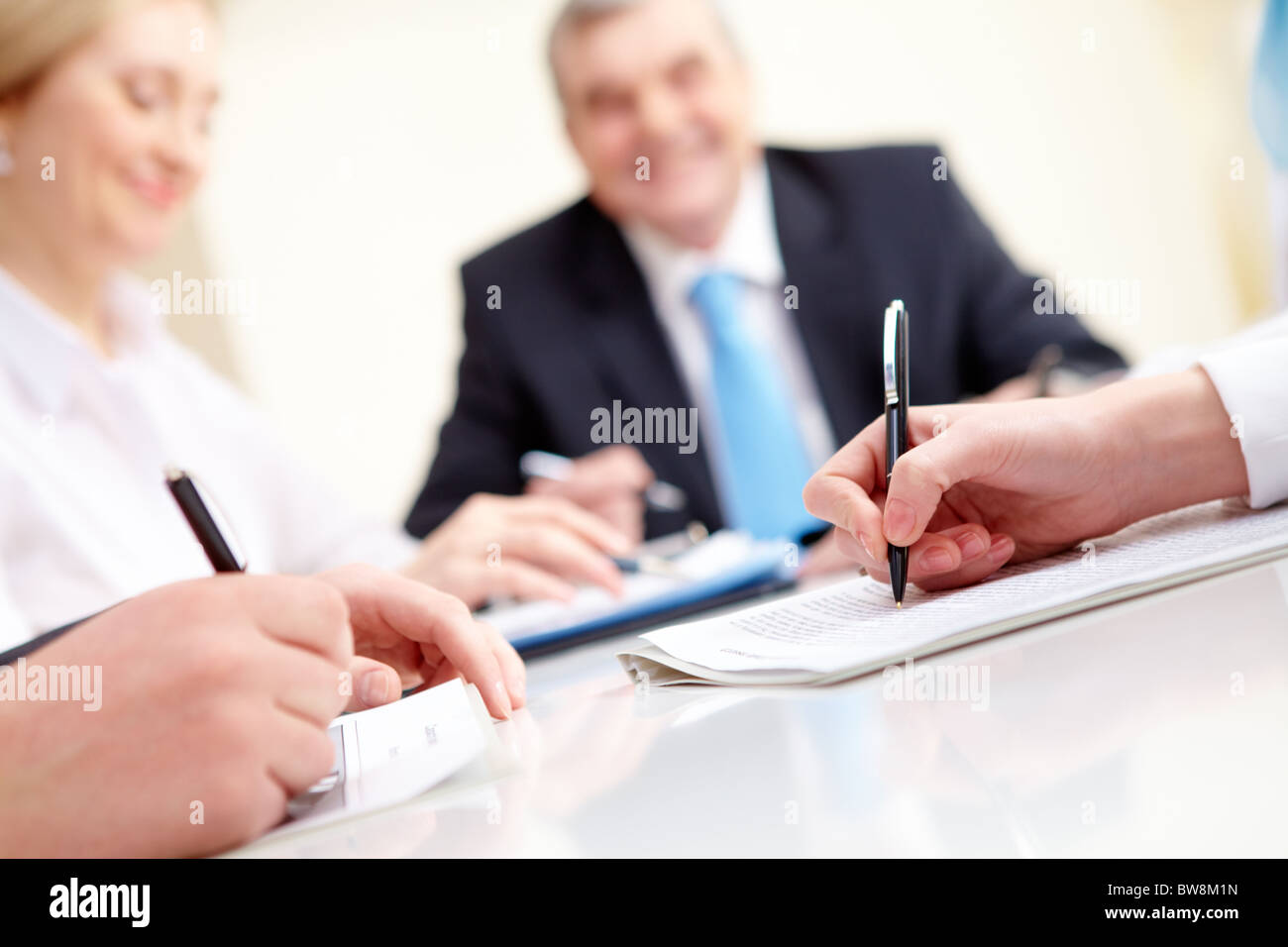 Close-up of business partners hands over document with their boss on background - Stock Image