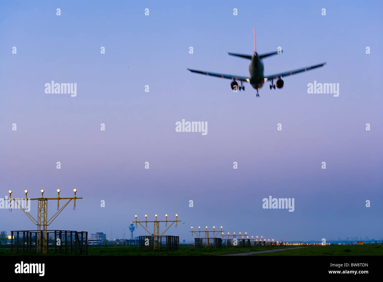 Amsterdam Schiphol Airport at dusk. Airplane plane approaching, landing, on the Kaagbaan runway. - Stock Image
