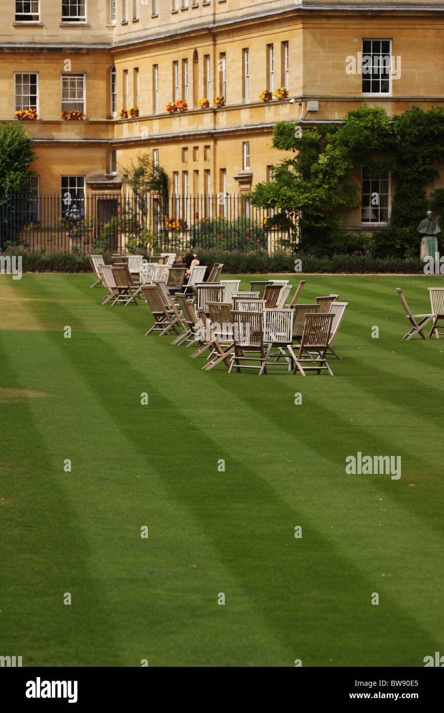 Vertical shot of formal garden with strips on the lawn and wooden chairs, with a grand house in the background. - Stock Image