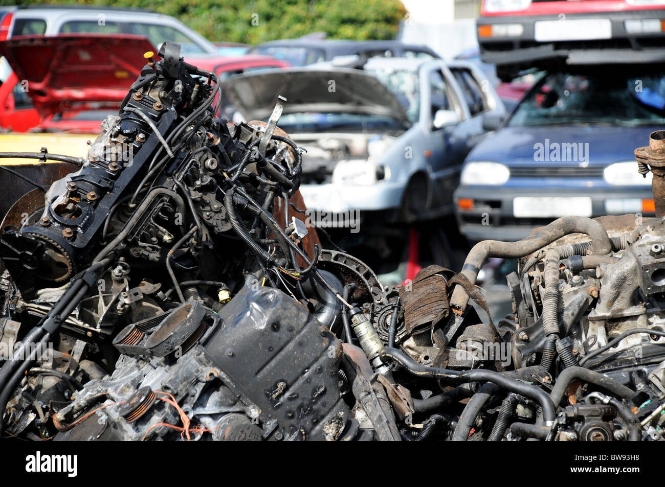 A pile of scrap car parts in skip with piles of scrap cars behind ...