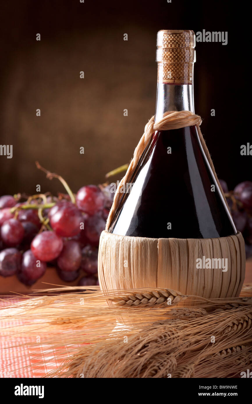 Wine Flask with Wheat and Red Grapes - Stock Image