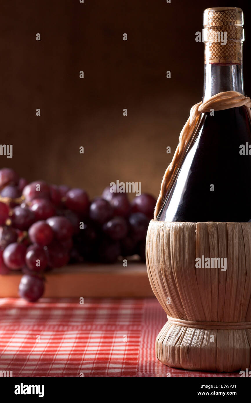 Wine Flask with Red Grapes - Stock Image