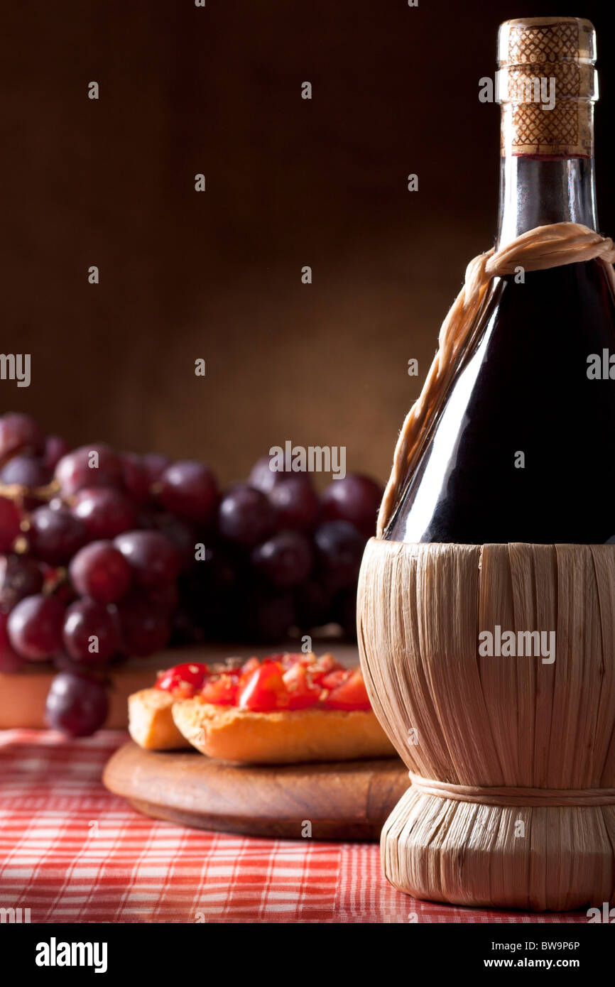 Wine Flask with Bruschetta and Red Grapes - Stock Image