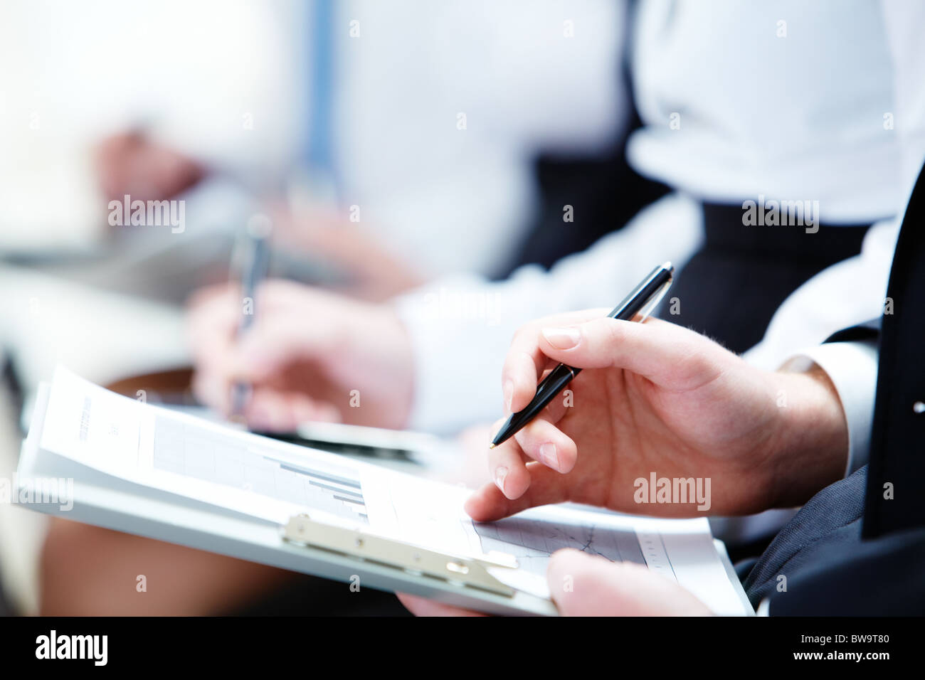 Image of business person hands with documents making notes at the lecture - Stock Image