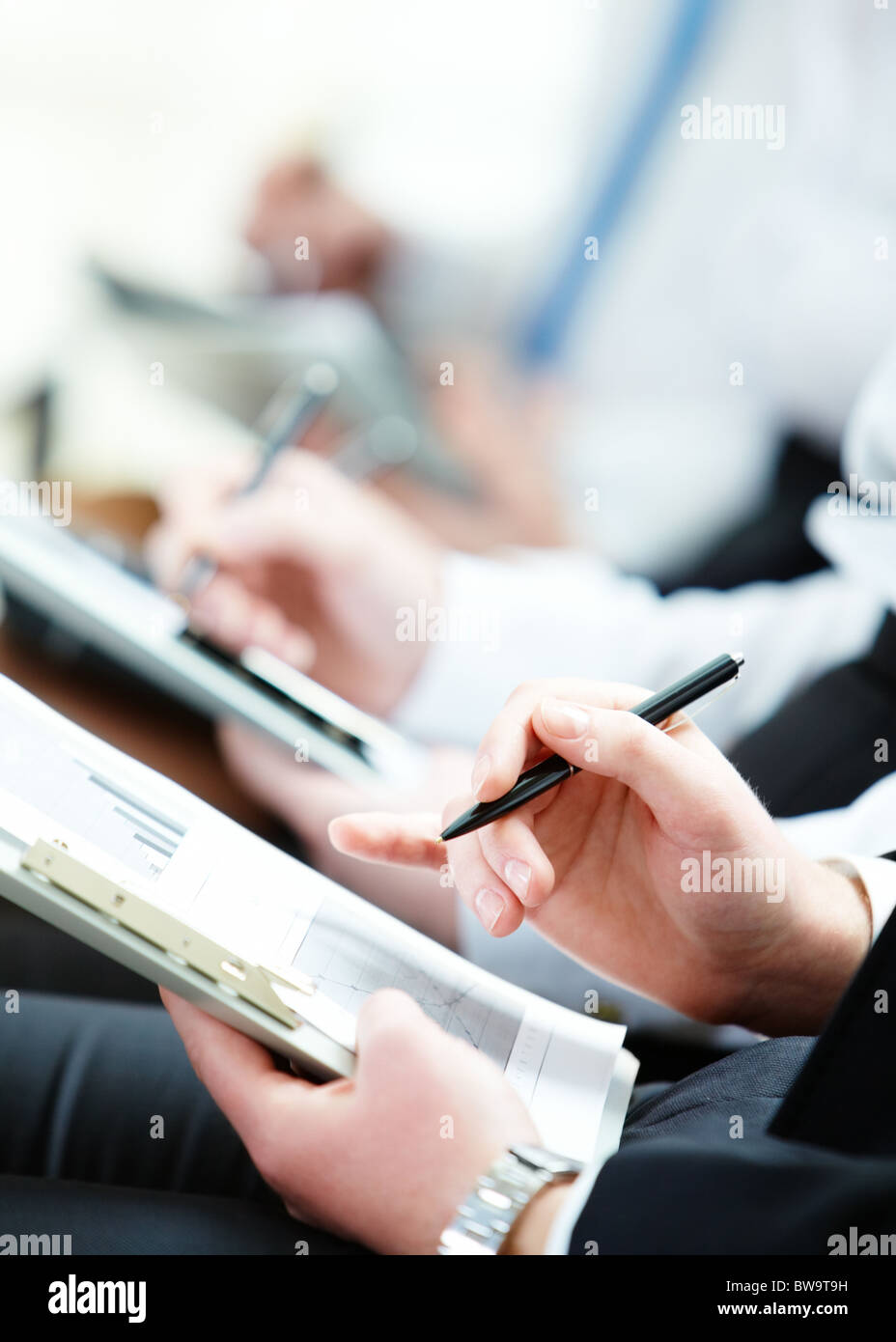 Business person hand with pen pointing at document during lecture - Stock Image