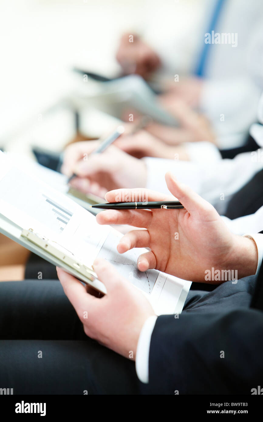 Business person hand with pen learning document during lecture - Stock Image