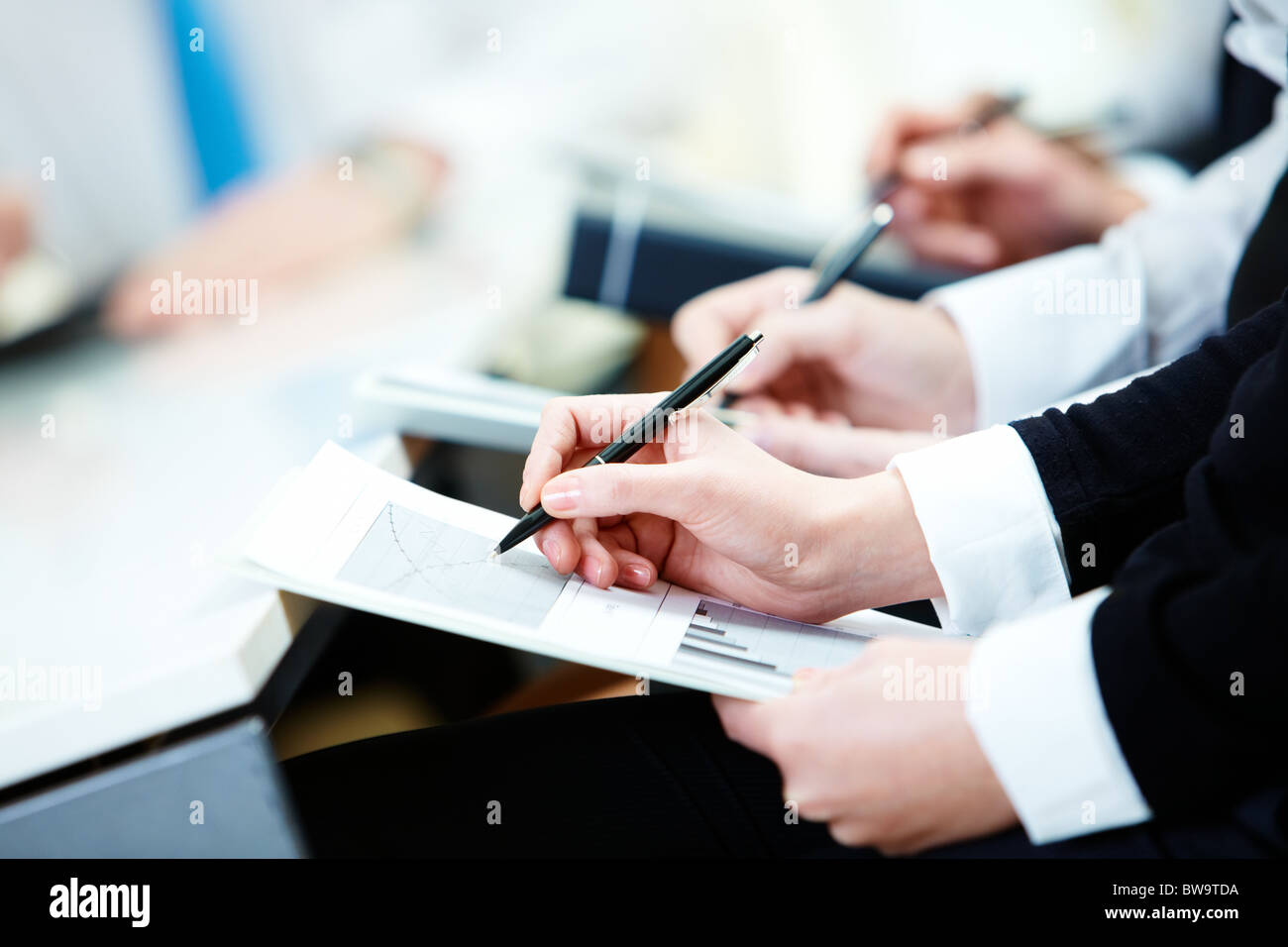 Close-up of business person hands with document writing at lecture - Stock Image