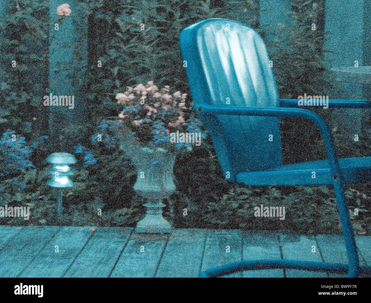 grainy shot of old blue chair with flowers on wood deck. - Stock Image