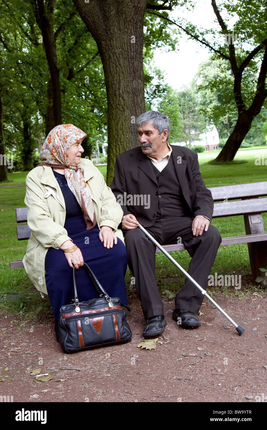 An elderly Turkish couple sitting on a bench in a park, Herne, Germany - Stock Image