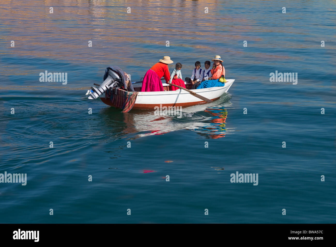Skiff filled with indigenous people in costume being rowed by a woman, Uros Islands, Lake Titicaca, Puno, Peru - Stock Image