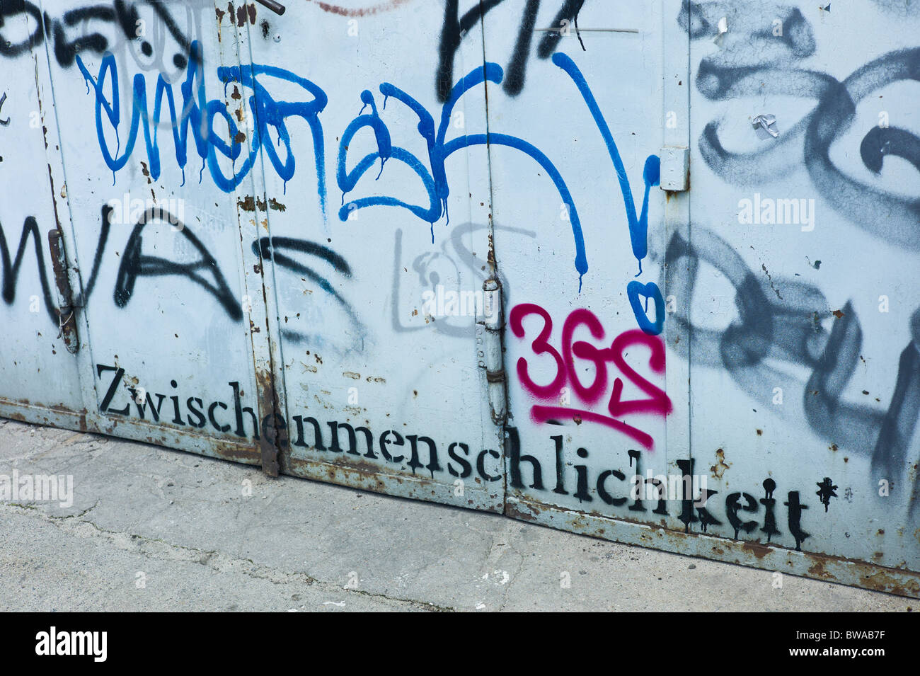 Greyish steel gate covered with tacks and the word 'Zwischenmenschlichkeit', Treptow Arena, Berlin, Germany - Stock Image