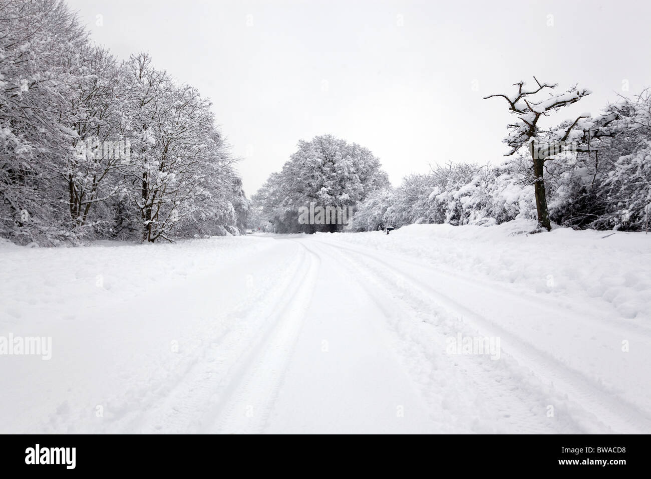 Tyre tracks in the snow on a rural road in England - Stock Image
