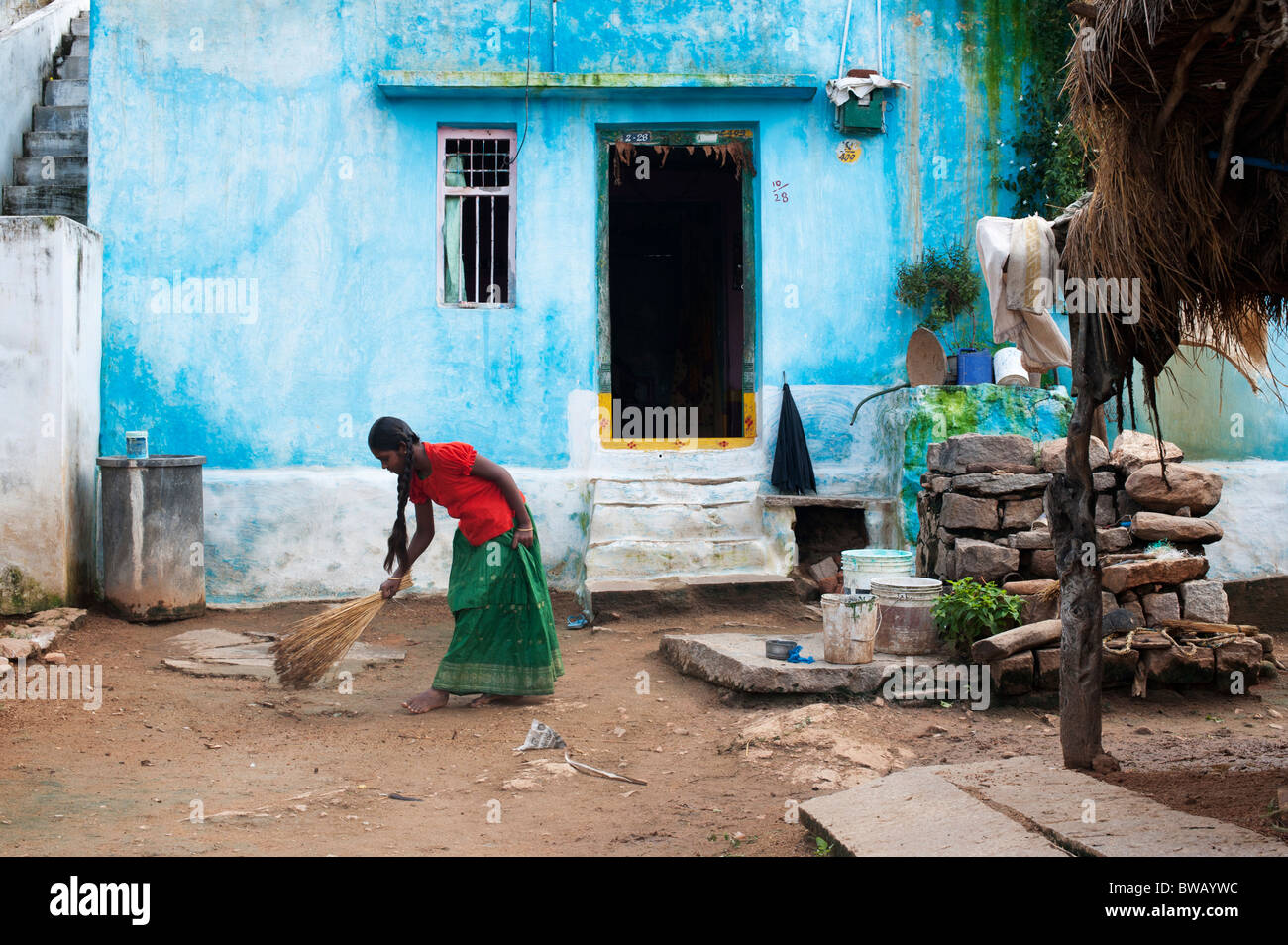 Young indian girl sweeping the front yard of her home in a rural indian village. Andhra Pradesh, India Stock Photo