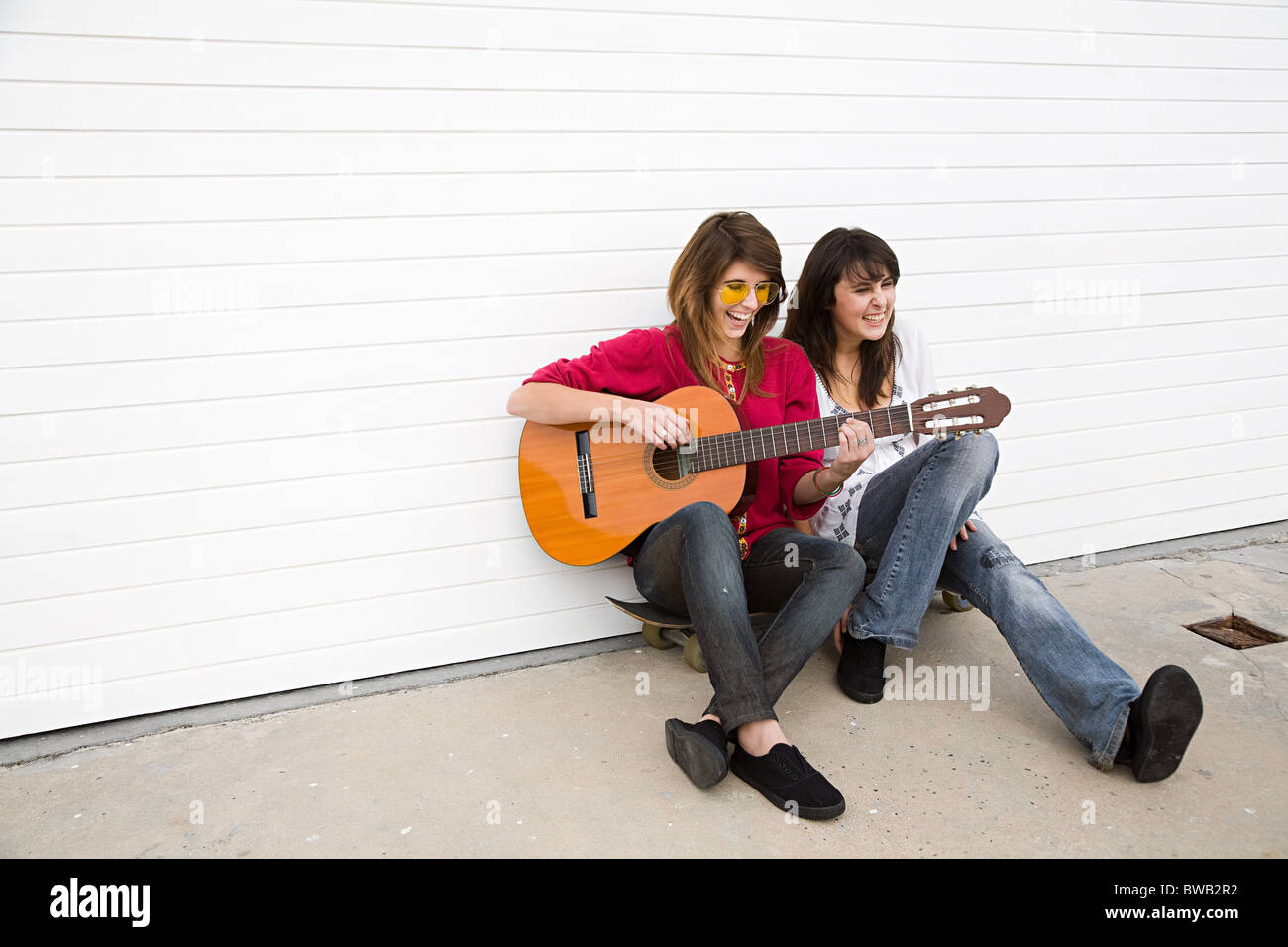 Two girls sitting on floor with guitar - Stock Image