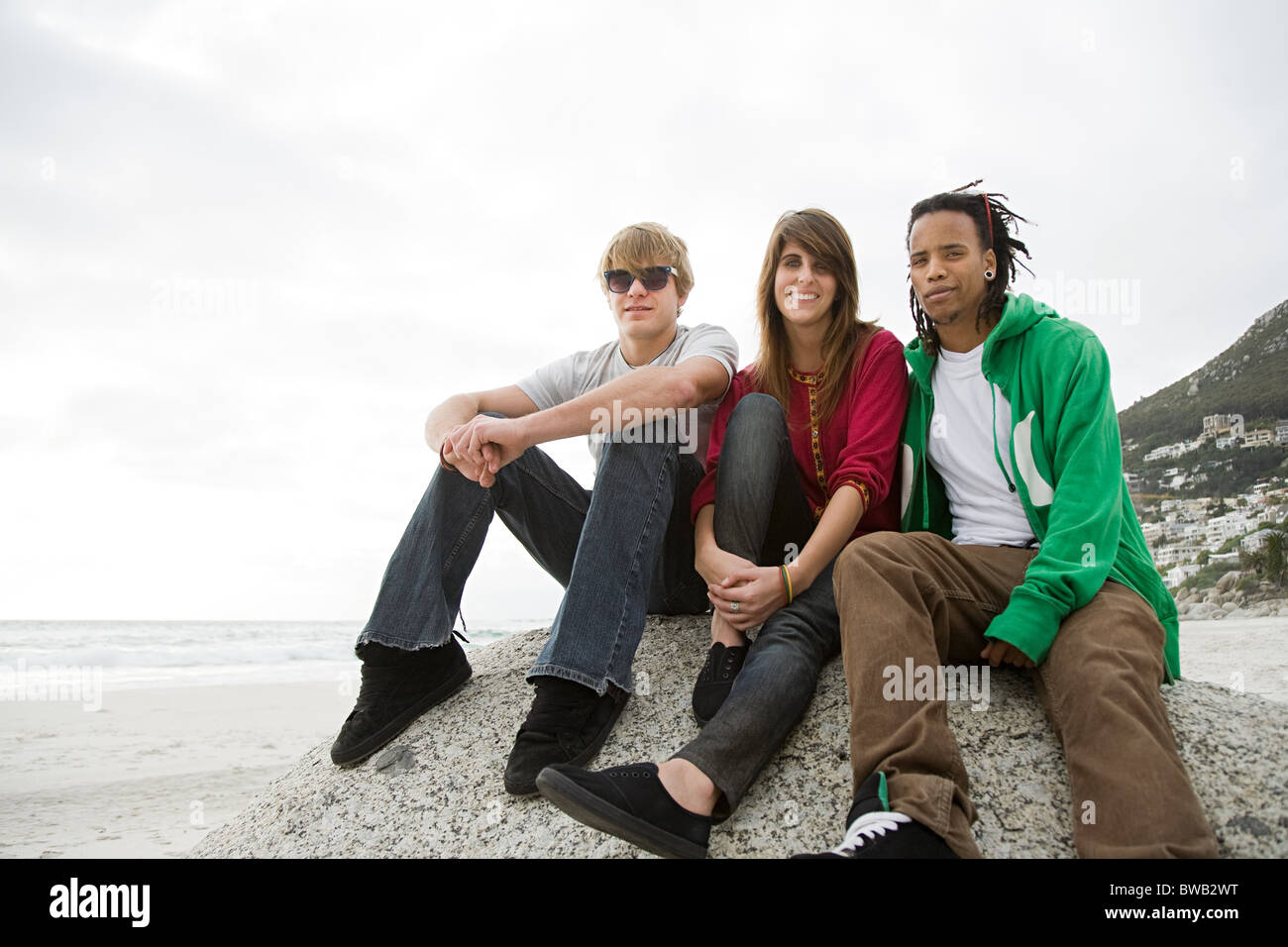 Group of friends sitting on boulder - Stock Image