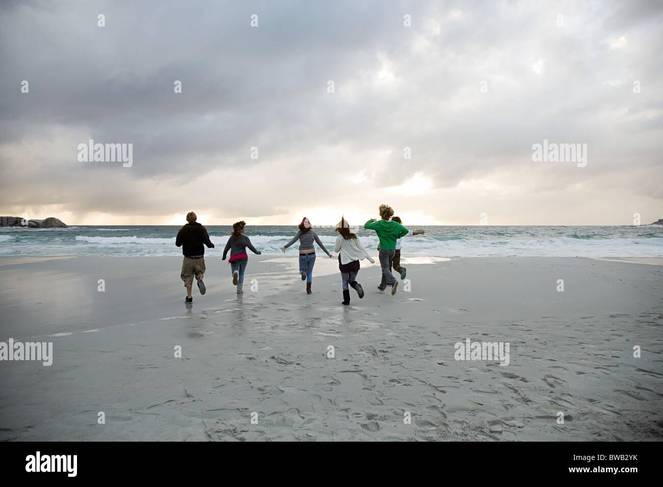 People running on beach - Stock Image