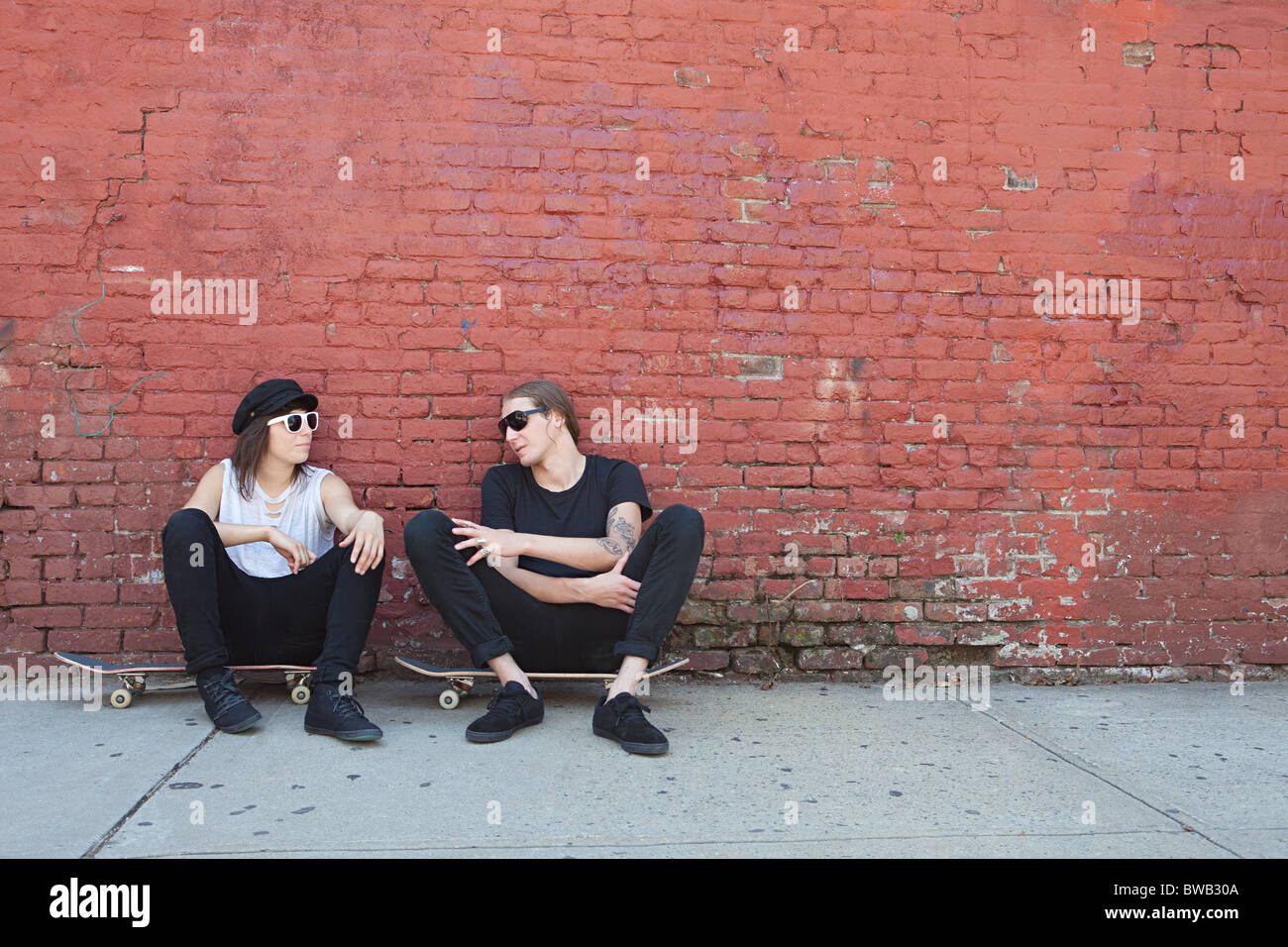 Skaters sitting on boards by wall - Stock Image