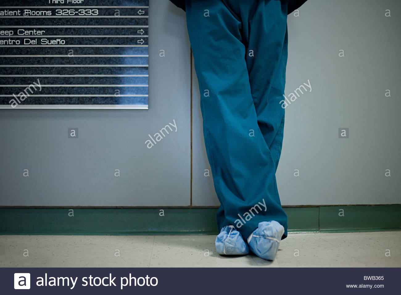 Hospital surgeon wearing shoe protectors, low section - Stock Image