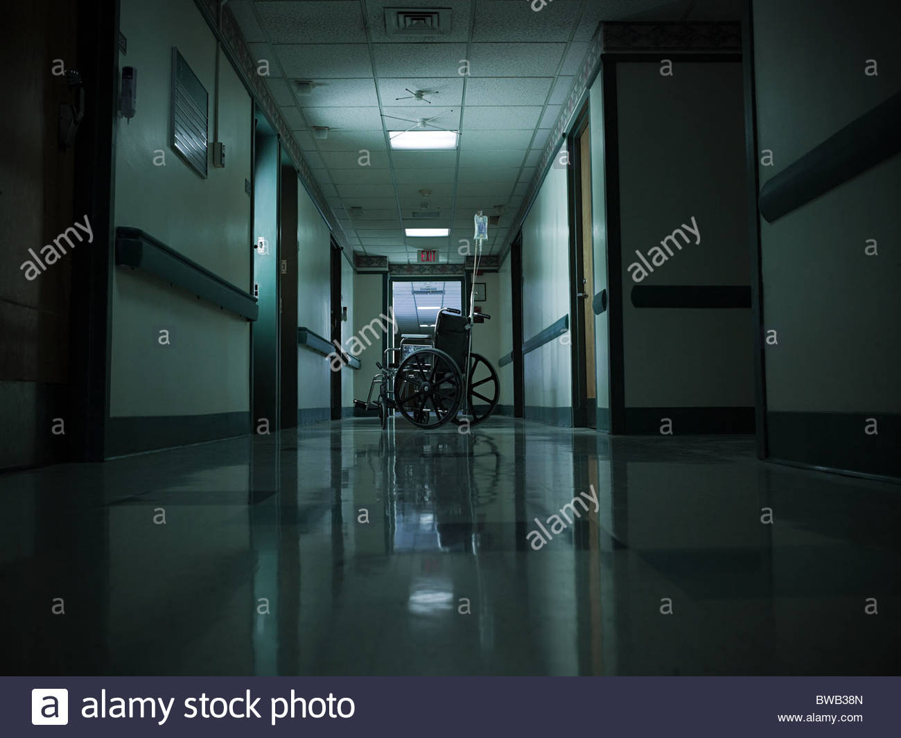 Empty wheelchair and intravenous drip in hospital corridor - Stock Image