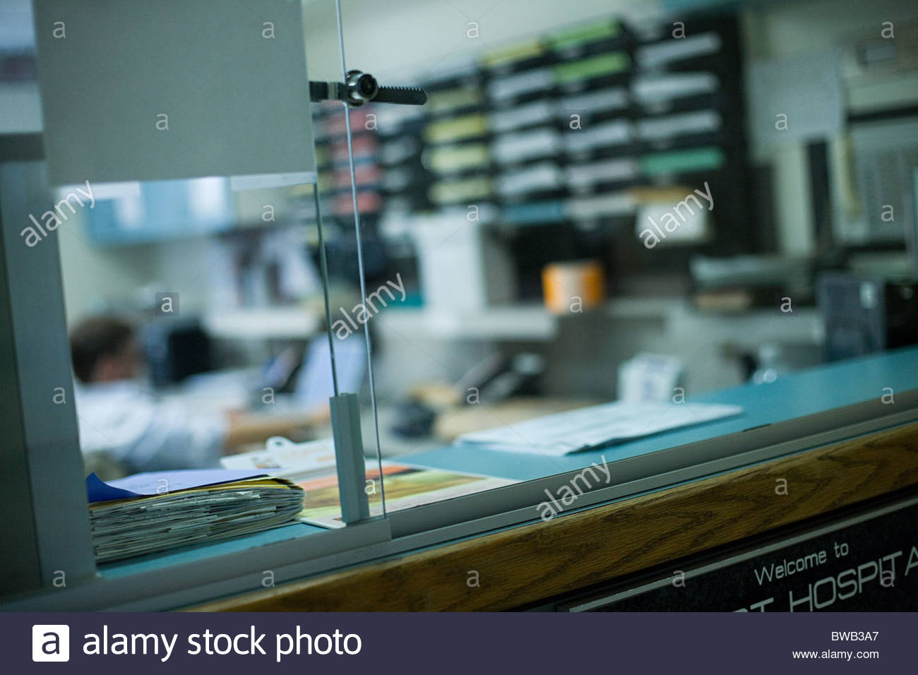 Hospital employee working in reception - Stock Image