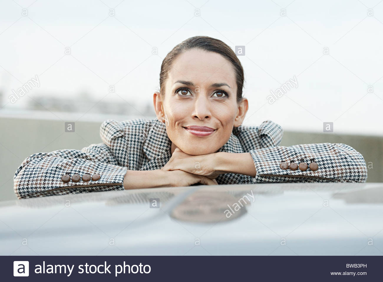 Businesswoman leaning on car roof - Stock Image