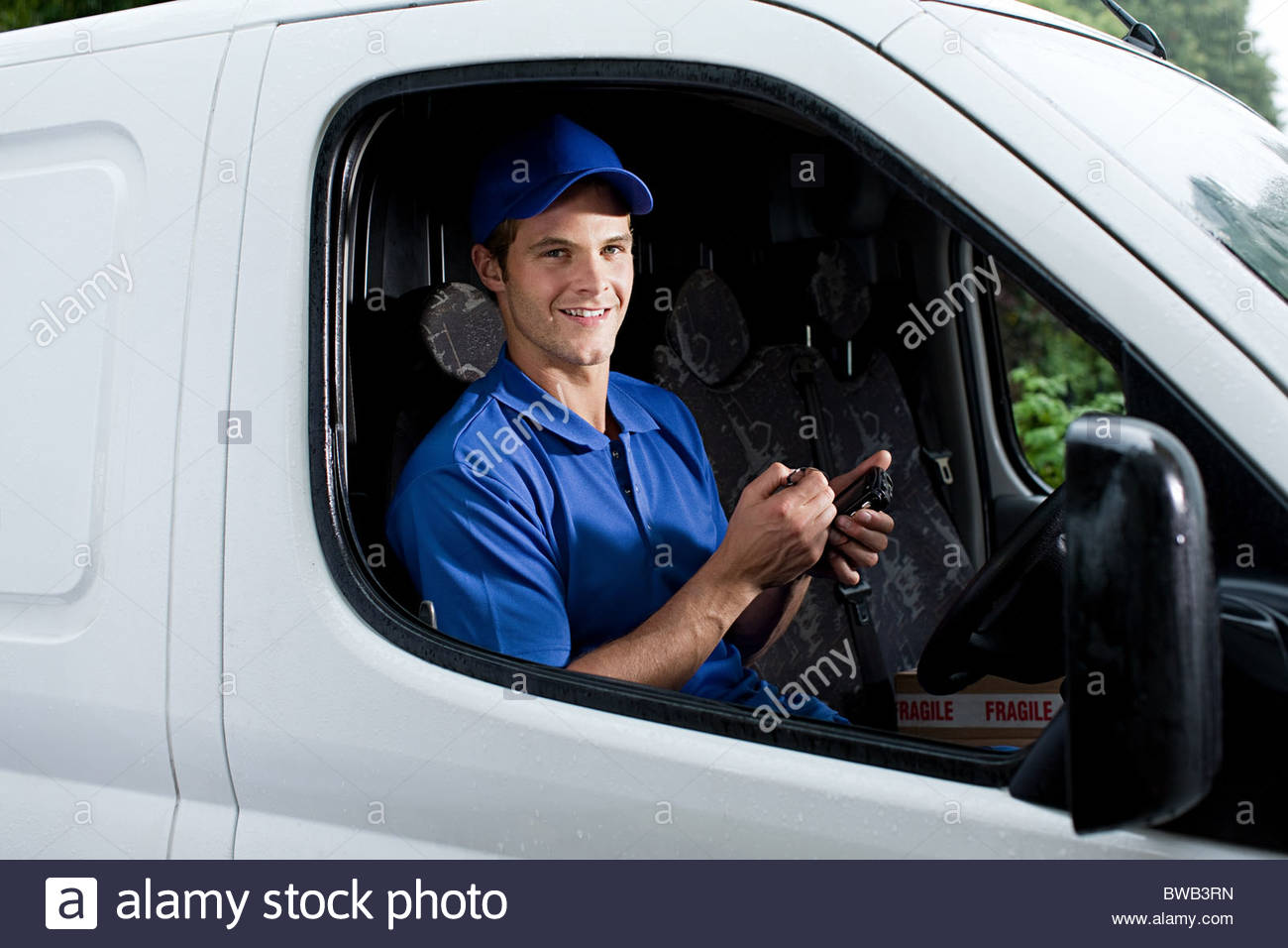 Delivery man in van with handheld computer - Stock Image