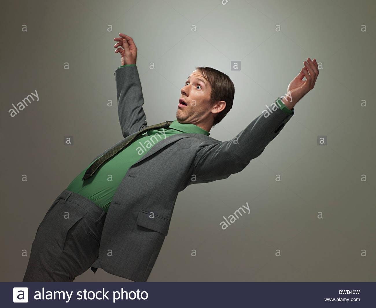 Mid adult businessman falling backwards, portrait - Stock Image
