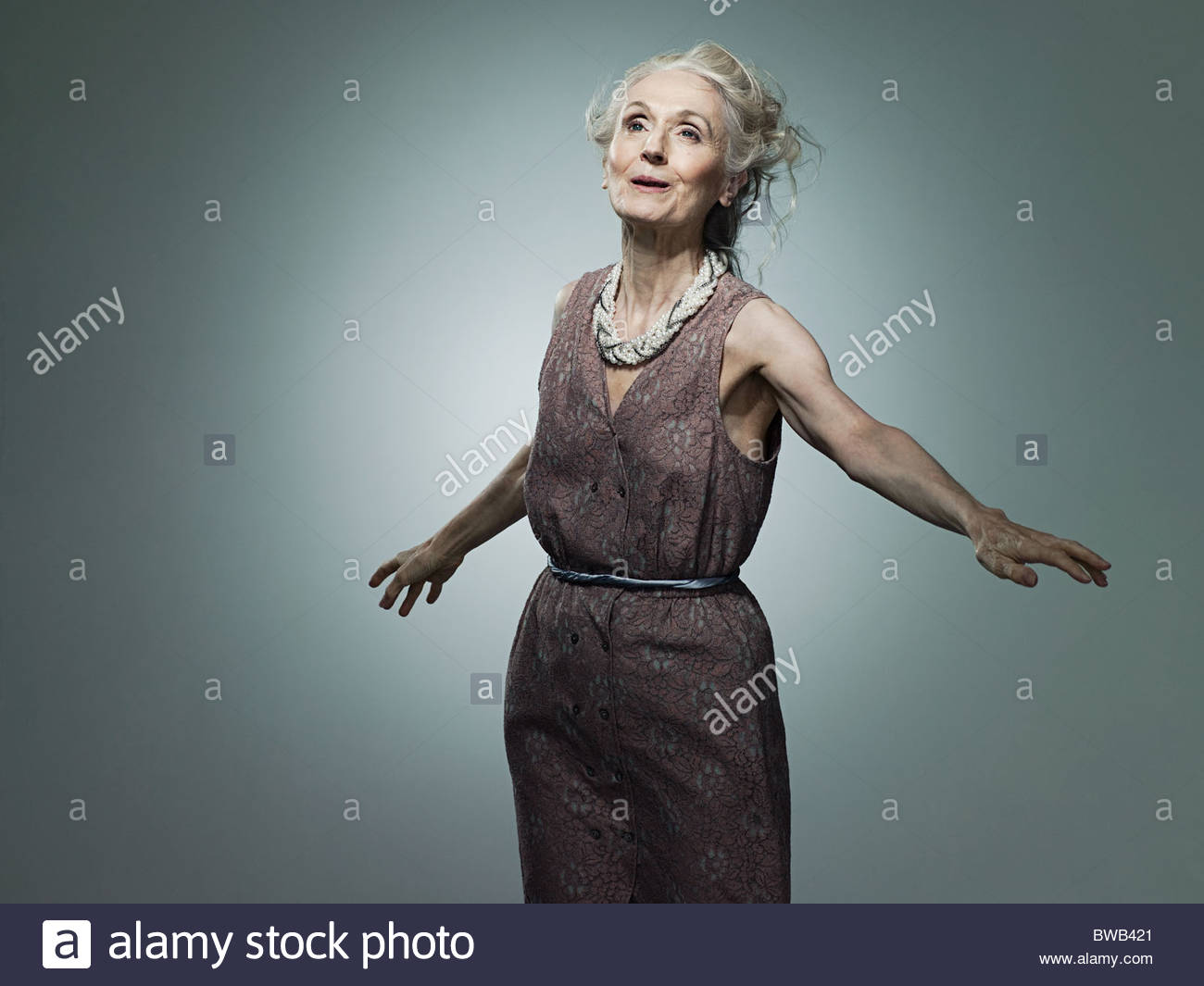 Senior woman with arms out, portrait - Stock Image