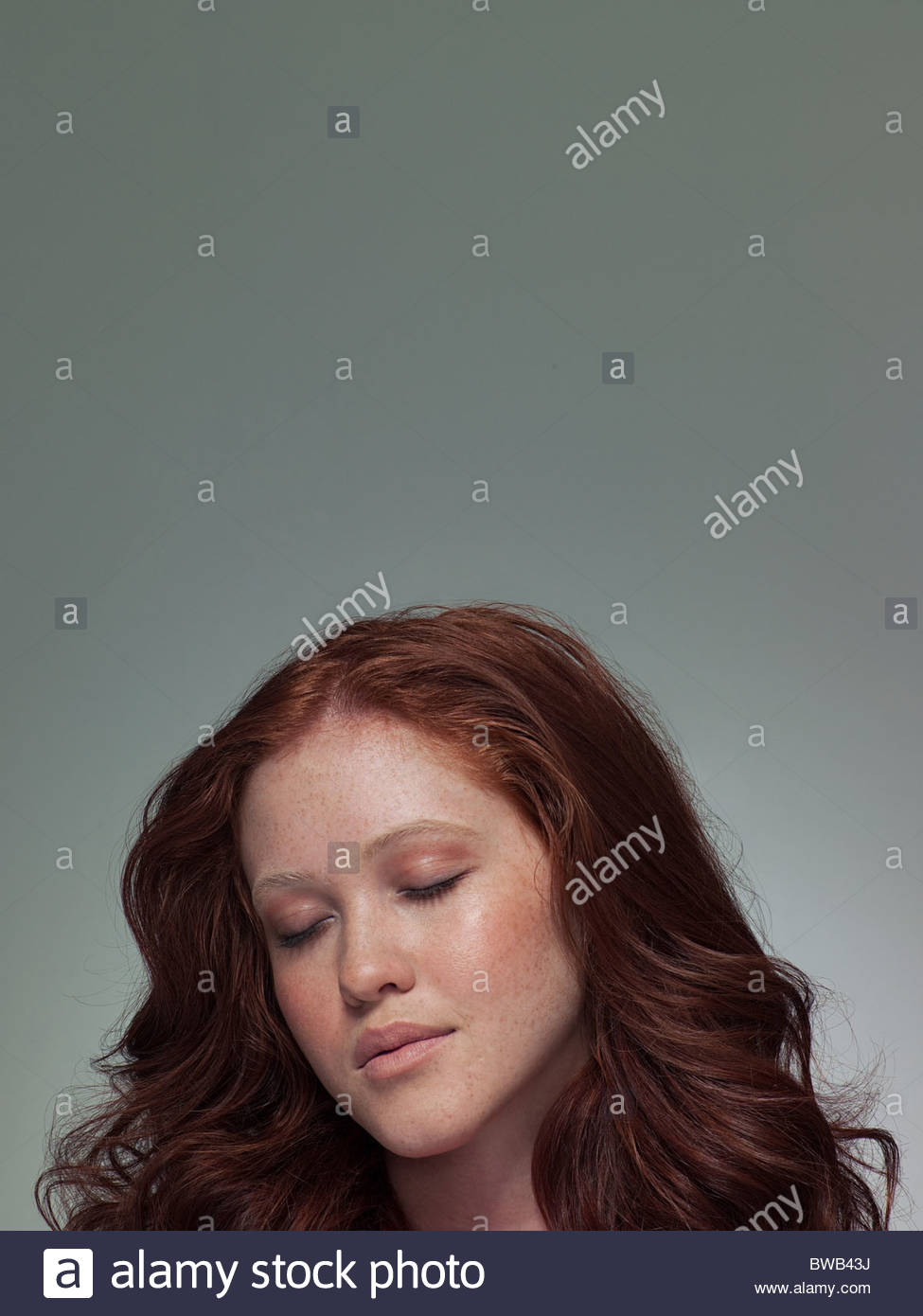 Head shot of young woman with eyes closed, portrait - Stock Image