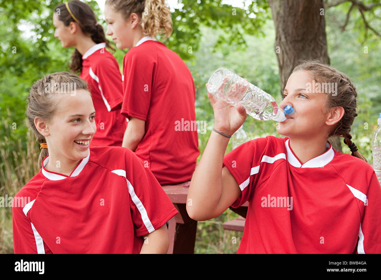 Girl soccer players drinking water - Stock Image