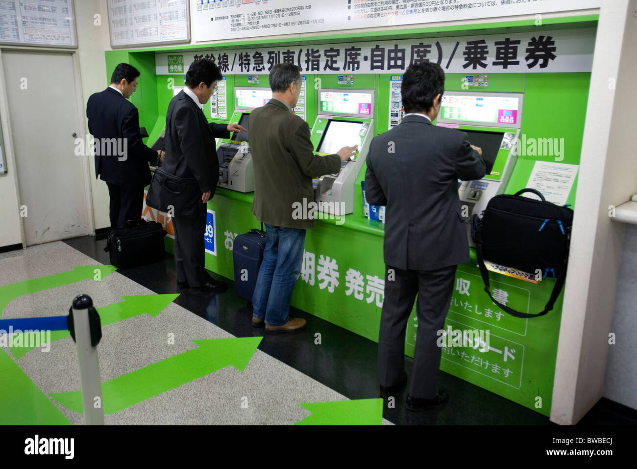 Men buying a JR ticket from automatic machines, Hiroshima, Japan. - Stock Image